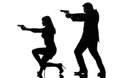 Couple woman man detective secret agent criminal silhouette. One caucasian men detective secret agent criminal with gun in silhouette studio isolated on white royalty free stock image