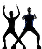 Couple woman man exercising workout. Couple women men exercising workout fitness aerobics posture in silhouette studio isolated on white background Royalty Free Stock Photos