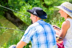Couple, woman and man, with fishing rods sport angling. Couple, women and man, sitting at river side with fishing rods angling for sport Stock Photo