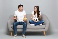 Couple woman man football fans cheer up support favorite team with soccer ball holding glass bowl of chips swearing stock images
