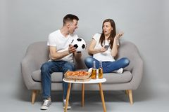 Couple woman man football fans cheer up support favorite team with soccer ball, using mobile phone, swearing isolated on. Couple women men football fans cheer up royalty free stock image