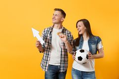 Couple, woman man, football fans holding bitcoin, metal golden coin, up arrow, soccer ball, cheer up support team. Isolated on yellow background. Sport bet stock photography