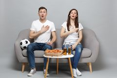 Couple woman man football fans in white t-shirt cheer up support favorite team singing hymn with hand on chest isolated. Couple women men football fans in white royalty free stock image