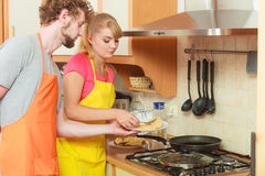 Couple woman and man frying chicken cutlet. Royalty Free Stock Photos