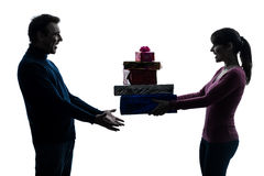 Couple woman man offering christmas gifts  silhouette Stock Photos