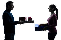 Couple woman man offering christmas gifts  silhouette Stock Photography