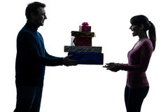 Couple woman man offering christmas gifts  silhouette Royalty Free Stock Photo