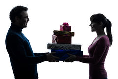 Couple woman man offering christmas gifts  silhouette Royalty Free Stock Photos