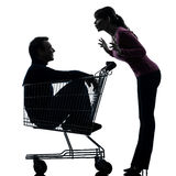 Couple woman  with man sitting in shopping cart silhouette Stock Image
