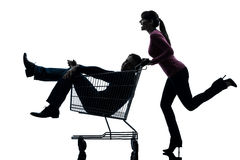 Couple woman  with man sitting in shopping cart silhouette. One caucasian couple women  with men sitting in shopping cart   in silhouette studio  on white Royalty Free Stock Photography