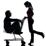 Couple woman  with man sitting in shopping cart silhouette. One caucasian couple women  with men sitting in shopping cart   in silhouette studio isolated on Stock Images