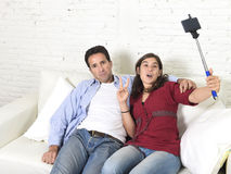 Couple with woman taking selfie photo with mobile phone and stick man tired and sick of pictures Stock Photography