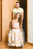 Couple with woman in wheelchair near door Royalty Free Stock Photo