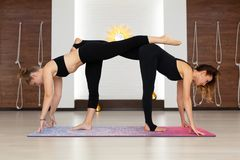 Couple womans in gym do yoga stretching exercises. Fit and wellness lifestyle stock image