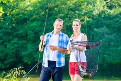 Couple sport fishing bragging with fish caught royalty free stock photography