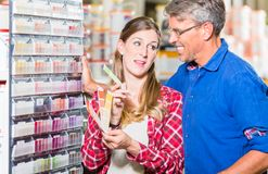 Couple choosing color of paint in hardware store Royalty Free Stock Image