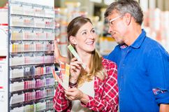 Couple choosing color of paint in hardware store. Couple, women and man, choosing color of wall paint in decoration department of hardware store royalty free stock image