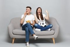Couple woman man football fans cheer up support favorite team with soccer ball, holding bowl of chips, clenching fists stock photography