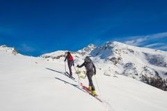 A couple of women practice ski mountaineering.  Royalty Free Stock Photography