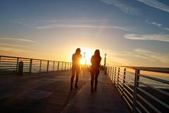 A couple of women walking into the sunset on the Hermosa Beach pier. Just another California coastal sunset. Aren`t we bored with them yet Stock Photo