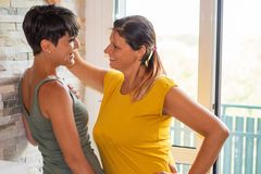 Couple of women watching in the eye each other with love. A couple of women watching in the eye each other with love stock photo