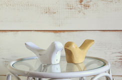 Couple of wood decor birds on vintage table. vintage filtered Stock Images