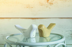 Couple of wood decor birds on vintage table. vintage filtered Stock Image