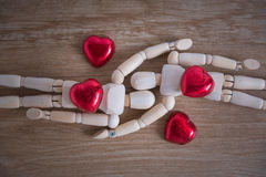 A couple of wooden doll man with heart-shaped chocolate Stock Images