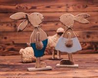 Couple of wooden easter bunnies near toy sheep Stock Photos