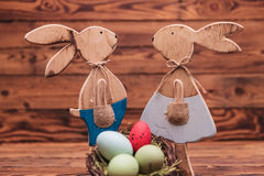 Couple of wooden easter bunnies standing near eggs basket Stock Photography