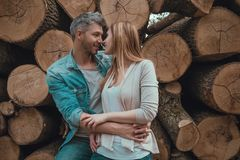 Couple wooden. Embracing couple in front of cutted trees royalty free stock photos