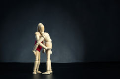 Couple of wooden figures hugging Stock Image