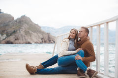 Couple on wooden pier near the sea in autumn Stock Photos
