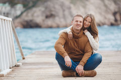 Couple on wooden pier near the sea in autumn Royalty Free Stock Image