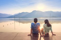 A couple on the wooden port at a lake on sunset Royalty Free Stock Photography