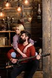 Couple in wooden vintage interior enjoy guitar music. Lady and man with beard on dreamy faces hugs and plays guitar. Couple in wooden vintage interior enjoy royalty free stock photo
