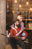 Couple in wooden vintage interior enjoy guitar music. Lady and man with beard on dreamy faces hugs and plays guitar. Couple in wooden vintage interior enjoy royalty free stock photos