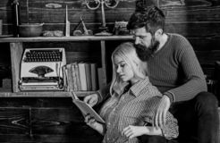 Couple in wooden vintage interior enjoy poetry. Romantic evening concept. Lady and man with beard on dreamy faces with. Couple in wooden vintage interior enjoy stock photography