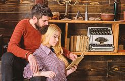 Couple in wooden vintage interior enjoy poetry. Romantic evening concept. Lady and man with beard on dreamy faces with stock images