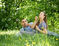 Couple in the woods blow bubbles Royalty Free Stock Photography