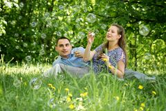 Couple in the woods blow bubbles Stock Photography