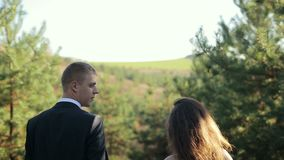 The couple in the woods bride and groom walking on edge of pine forest on the wedding day. Slow motion stock footage