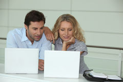 Couple at work on laptops Royalty Free Stock Photography