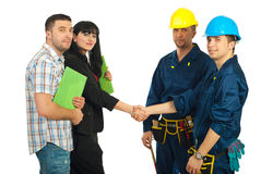 Couple and workers team agreement. Mid adult couple and workers team having an agreement and gives hand shake over white background Royalty Free Stock Photos