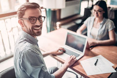 Couple working in cafe. Young couple in eyeglasses is working in cafe on laptops in front of each other. Handsome men is smiling and looking at the camera Stock Images