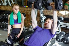 Couple working with dumbbells his body at gym. stock photo
