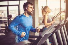 Treadmill exercise. Couple working exercise on treadmill. Focus is on man royalty free stock images