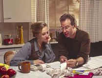 Couple working on finances. At kitchen table Stock Images