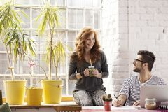 Couple working on freelance project. Young hipster couple working on freelance project in modern interior Stock Image