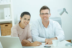 Couple working at home. Happy young casual couple sitting  at desk working together at home office, smiling Royalty Free Stock Image